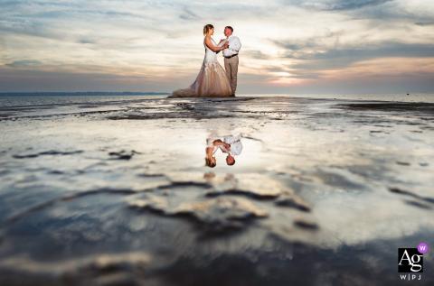 Portorož, Slovénie, portrait de mariage artistique d'un couple debout sur la jetée au coucher du soleil avec un reflet de l'eau de mer