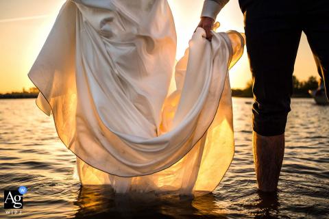 Loosdrechtse Plassen photo de mariage près de Kortenhoef du couple de mariage debout dans l'eau lors de leur mariage avec beaucoup de bateaux. Ils ont décidé de se promener dans l'eau. Il tient sa robe.