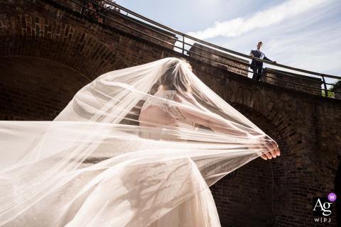 O fotógrafo de casamento em Leiden tirou esta imagem do noivo em cima da fortaleza de burcht e a noiva mostrando o véu