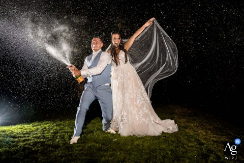 Netherlands couple is captured in this wedding photo shaking a bottle of champagne into the night sky at Brasserie Oostgaag