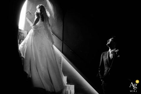 Nederland huwelijksportret van de bruidegom die zijn bruid bekijkt terwijl zij de trap naar het licht bij Kasteel Woerden loopt