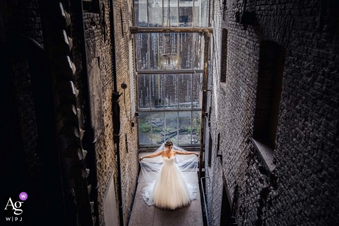 NL artistieke trouwfoto Bij de oude fabriek van de Sodafabriek in Schiedam De bruid toont haar jurk op de geweldige locatie die een mooi contrast vormt