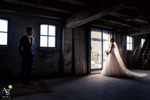Sodafabriek, Schiedam, Netherlands bride and groom posing during a portrait session at an old factory as the groom is looking at his beautiful bride, catching the nice window light