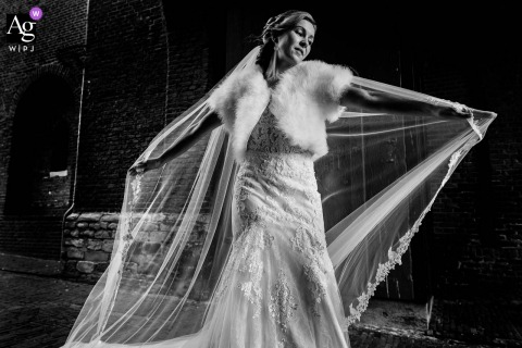Haarlem, NL wedding portrait of the bride showing her beautiful dress in the wind which blows through the Amsterdamse Poort