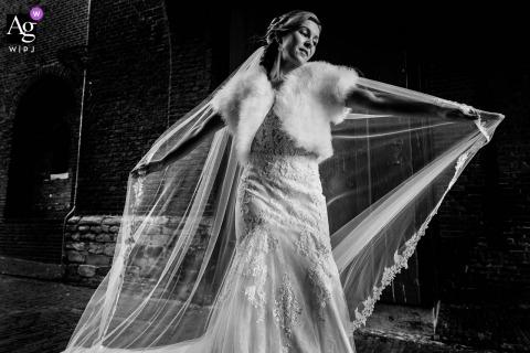 Haarlem, NL trouwportret van de bruid die haar prachtige jurk laat zien in de wind die door de Amsterdamse Poort waait