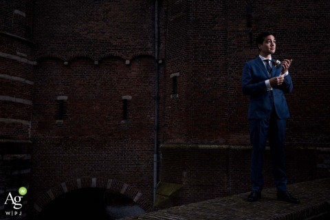 Haarlem, Netherlands groom posing for a wedding picture standing in front of the Amsterdamse Poort and checking his suit for a cool portrait
