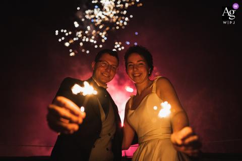 Brissac-Quincé, França, imagem do casamento da noiva e do noivo com fogos de artifício voando atrás deles no céu e brilhos nas mãos
