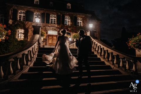 Schloss Linnep, Ratingen, Alemanha Casal de noivos filma à noite nas escadas da frente do local sob as luzes