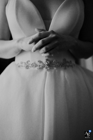 Poland at-home artistic wedding photo from Zachodniopomorskie of the bride's nervous hands while the bridesmaid is fastening her wedding dress