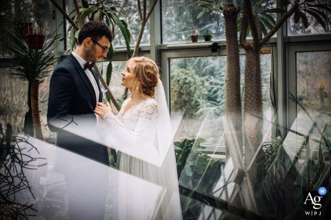 De huwelijksfotograaf van Lodz legt de jonggehuwden vast die knuffelen in het palmenhuis in Yuca Wedding Hal