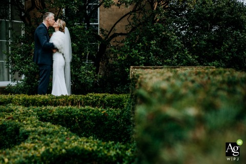 England wedding bride and groom share a kiss in the gardens of their wedding venue