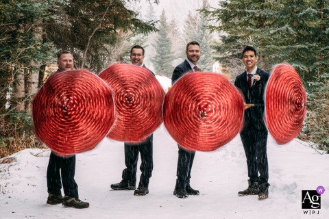 AB, Canada Wedding Photographer of the groom with his groomsmen playing with umbrellas at Cornerstone Theater in Canmore