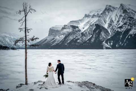 AB artistic wedding pic from Cornerstone Theater, Canmore, Canada	of the couple in winter holding the hands