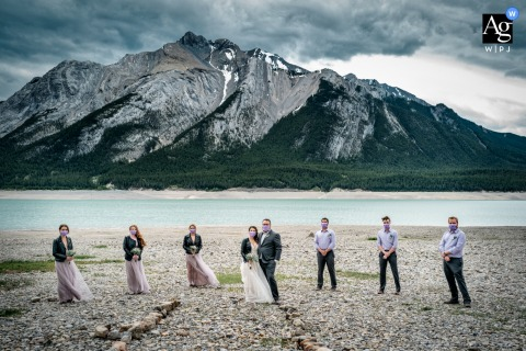 AB artistic wedding portrait showing the bridal party at the mountains and Abraham Lake and staying 2 meters apart
