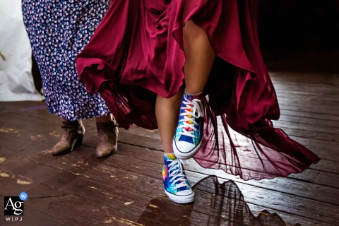 A PA artistic wedding photo of a Bridesmaid dancing in tie dyed rainbow chucks at Desmond Hotel Malvern Pennsylvania wedding
