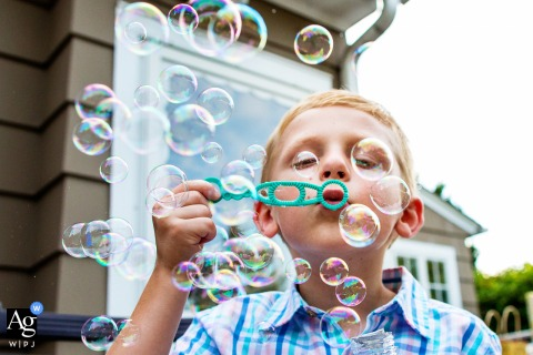Artistic wedding photo created at home as the Couple's nephew blows bubbles during backyard intimate wedding in NJ