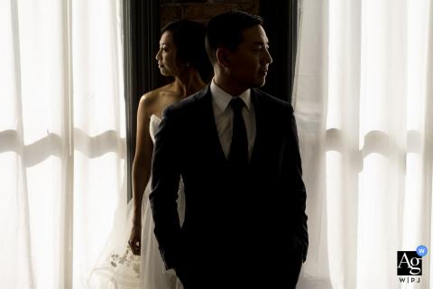 Foto di matrimonio artistico dal centro di Seattle Studio della sposa e dello sposo in piedi contro una finestra luminosa
