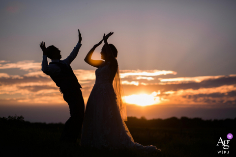 A Detroit Lakes, Minnesota high five during the sunset in this artistic wedding photo