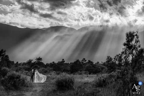 Lijiang, China fine art wedding photography Bride and groom portrait under shafts of light coming through the clouds