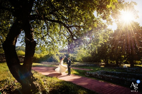Krakra Fortress, Bulgaria fine art wedding photography of the Bride and groom dancing under the sunrays in the trees on a walkway