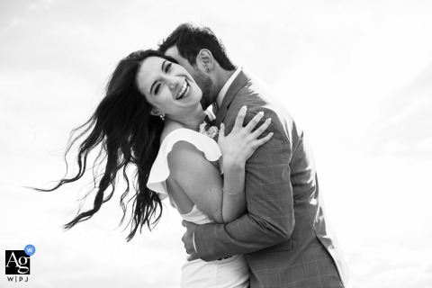 Edmonton, Alberta creative wedding day portrait shoot with the bride laughing while embracing groom against a background of the white sky