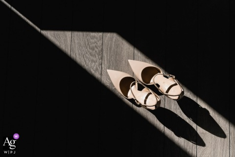 Madrid, Spain creative wedding Bridal shoes detail picture on wood floor with sunlight shaft