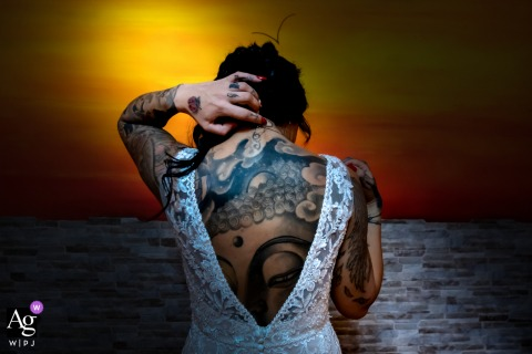 Casa della sposa, Marmirolo, Mantova, Italia creative bridal portrait showing the The strong color of the bedroom and the aggressiveness of the tattoos, combined with the sweetness of the gesture and the white dress, tell the character extremes
