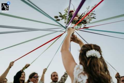 Les Serres, Ile de Ré, France creative, fine art wedding photo of the cutting of the ribbons with the bouquet