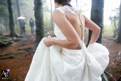 Black Balsam Knob, NC creative wedding detail image of the Bride holds dress while walking down the aisle in the forest of trees in the fog
