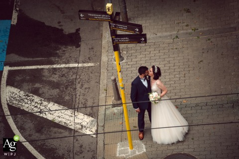 Bulgaria couple posing for wedding images of the bride and groom kissing on the street sidewalk