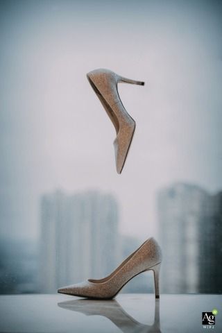 China wedding detail picture of the bride's wedding shoes hanging in the air with the cityscape behind
