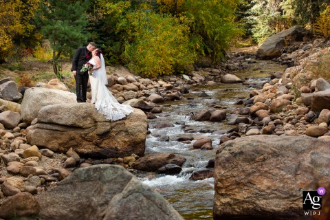 Estes Park Condos, Estes Park, Colorado retrato de casamento de casal criativo em uma rocha enorme com vista para o rio que atravessa o espaço da recepção