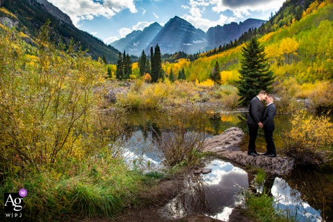 Maroon Bells, Aspen Colorado fine art wedding portrait of a kiss on a small island in front of the Maroon Bells Peaks