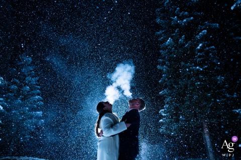 Vail, Colorado, retrato de casamento criativo do casal vendo sua respiração se iluminar enquanto a neve cai ao redor deles
