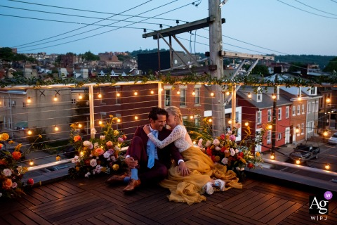 Lawrenceville, Pittsburgh, PA fine art wedding portrait of The bride and groom enjoying a private moment together at dusk on the rooftop where they got married
