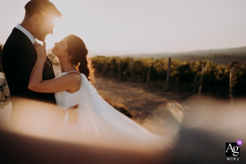 Farm of Corsignano fine art wedding couple portrait created while the couple is standing, face to face as they embrace with complicity, the sun filters behind them, pushed by the wind the veil of the bride disappears on the first floor