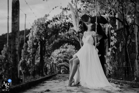 Villa Garavaglia creative wedding day portrait created as the bride is sitting on a swing while the groom kisses her from behind