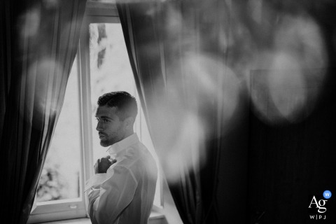 Villa Garavaglia creative wedding portrait of the groom during the getting ready, the shooting is done from above so as to take advantage of the effect of dim lights offered by an antique chandelier hanging from the ceiling