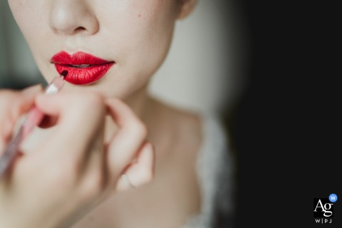 Napoli creative, fine art wedding photo of the bride having bright red lipstick applied to her lips