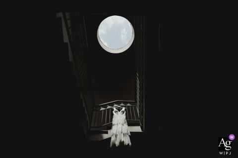 Napoli creative wedding detail image of the dress hanging below a round skylight window
