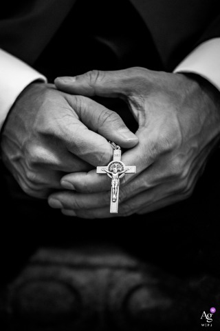 Chicago, Illinois fine art wedding picture of the groom holding the cross in his hands