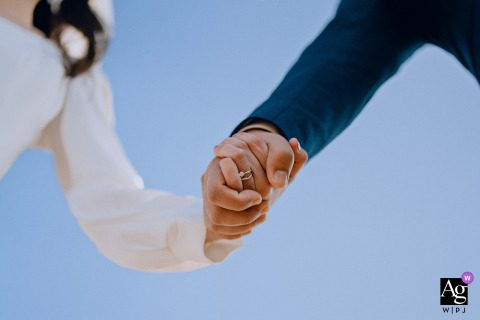 Nanping, Fujian fine art wedding detail pic showing The hands clasped by the bride and groom during the ceremony below the blue sky
