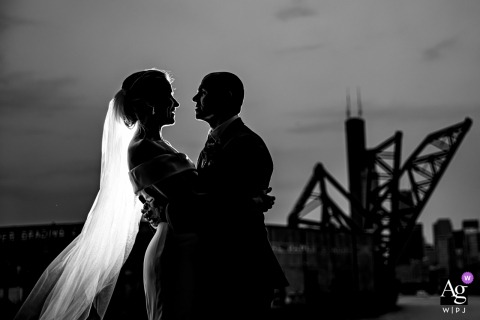 Chicago, Illinois creative wedding day portrait silhouetted against skyline with a draw bridge