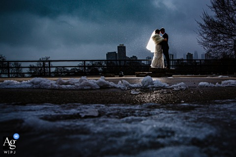 Chicago, Illinois fine art wedding portrait of a couple in the snow with a single light at dusk