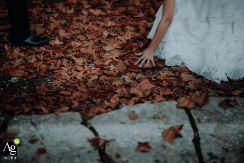 Creative wedding detail image from Quinta dos Alfinetes, Sintra, Portugal of the bride grabbing leaves from a fallen maple tree with the Autumn arrival