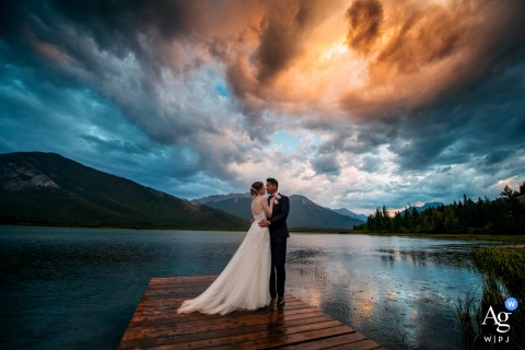 Vermilion Lakes, AB, Canada fine art wedding portrait of the Rain and sunset and a married couple