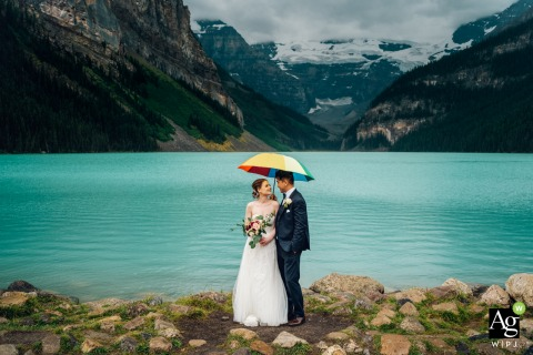 Creative wedding portrait at Lake Louise, Banff National Park on a rainy day