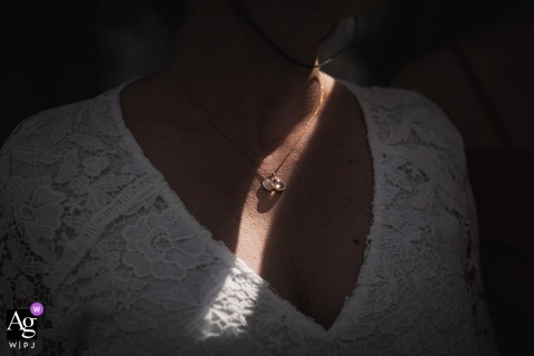 Saint Pabu, France fine art wedding picture of the bride and her necklace in a sliver of light