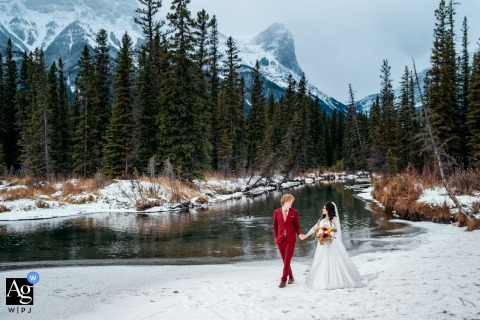 Canmore, AB, Canada creative wedding day portrait of the Bride and groom holding the hands after the ceremony