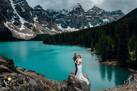 Moraine Lake, AB, Canada fine art wedding portrait of a Married couple in love posing over the blue lake